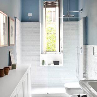 Ispirazione per una piccola stanza da bagno con doccia bohémian con pareti blu, pavimento multicolore, ante con riquadro incassato, ante bianche, doccia alcova, pavimento con piastrelle in ceramica e porta doccia a battente