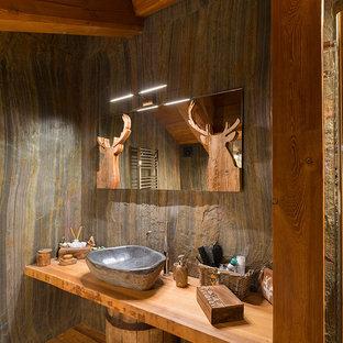 Ispirazione per una stanza da bagno rustica con pavimento in legno massello medio, lavabo a bacinella e top in legno