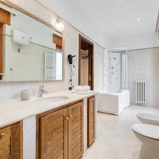 Esempio di una grande stanza da bagno padronale mediterranea con ante a persiana, ante in legno chiaro, vasca idromassaggio, vasca/doccia, piastrelle bianche, piastrelle a mosaico, lavabo sottopiano e top in pietra calcarea