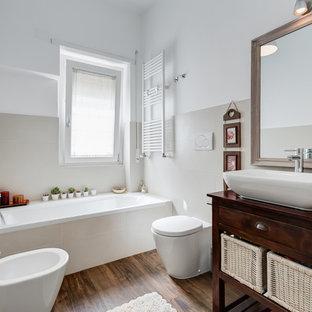 Diseño de cuarto de baño principal, contemporáneo, de tamaño medio, con armarios abiertos, puertas de armario de madera en tonos medios, bañera esquinera, bidé, baldosas y/o azulejos beige, paredes beige, suelo de madera oscura, lavabo sobreencimera, encimera de madera y encimeras marrones