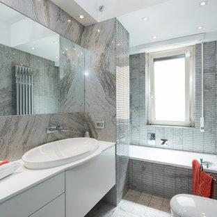 Foto di una stanza da bagno padronale minimal con ante lisce, ante bianche, vasca da incasso, piastrelle grigie, piastrelle a listelli, lavabo da incasso e doccia aperta