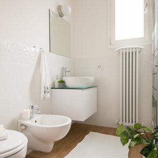 Свежая идея для дизайна: ванная комната среднего размера в современном стиле с плоскими фасадами, биде, белой плиткой, белыми стенами, светлым паркетным полом, настольной раковиной и стеклянной столешницей - отличное фото интерьера