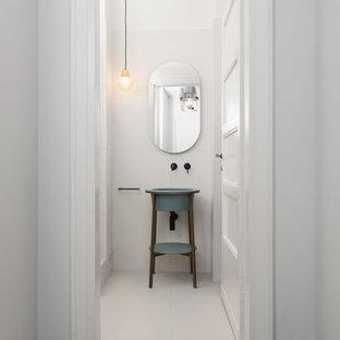 Foto di una stanza da bagno con doccia moderna con ante lisce, doccia ad angolo, WC sospeso, piastrelle bianche, piastrelle in ceramica, pareti bianche, pavimento con piastrelle in ceramica, lavabo a colonna, pavimento bianco, porta doccia a battente e top blu