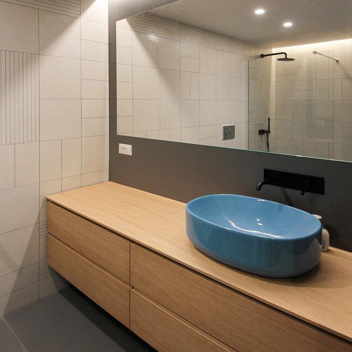 L'area lavabo è caratterizzata da un grande mobile con cassetti in legno di rovere, su cui poggia una bacinella colore turchese della casa NIC DESIGN, e da un grande specchio che occupa l'intera largh
