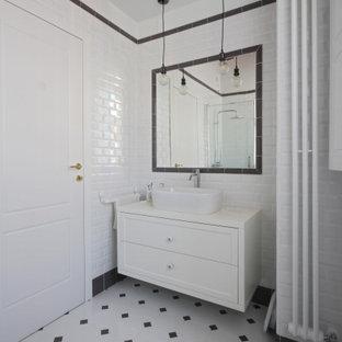 Foto på ett mellanstort lantligt vit badrum med dusch, med luckor med infälld panel, vita skåp, en hörndusch, en toalettstol med separat cisternkåpa, svart och vit kakel, tunnelbanekakel, vita väggar, mosaikgolv, ett fristående handfat, träbänkskiva, flerfärgat golv och dusch med skjutdörr