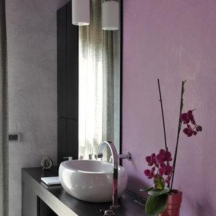 Idee per una stanza da bagno padronale contemporanea con ante nere, vasca freestanding, WC sospeso, pareti viola, pavimento con piastrelle in ceramica, lavabo a bacinella, top in legno, pavimento nero e top nero