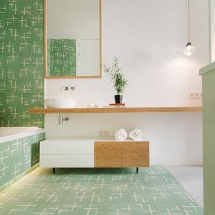 Imagen de cuarto de baño principal, actual, con armarios abiertos, puertas de armario de madera oscura, bañera encastrada, baldosas y/o azulejos verdes, lavabo sobreencimera, encimera de madera, suelo verde, paredes blancas y encimeras beige