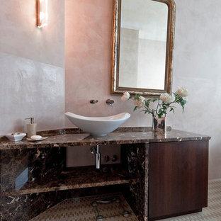 Modelo de cuarto de baño principal, ecléctico, grande, con armarios con rebordes decorativos, puertas de armario de madera oscura, bañera japonesa, sanitario de pared, paredes rosas, suelo de piedra caliza, lavabo sobreencimera, encimera de mármol y suelo beige