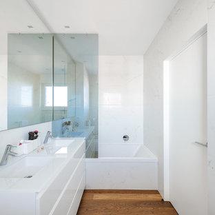 Idee per una stanza da bagno padronale design di medie dimensioni con ante lisce, ante bianche, vasca ad alcova, piastrelle bianche, lastra di pietra, pareti bianche, pavimento in legno massello medio, lavabo integrato, top in superficie solida e doccia aperta