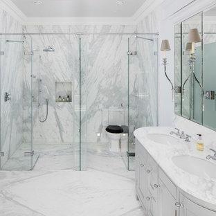 Ispirazione per una stanza da bagno padronale classica con doccia a filo pavimento, pareti bianche, pavimento in marmo, lavabo sottopiano, porta doccia a battente, ante a filo, ante grigie, piastrelle bianche, piastrelle di marmo, top in marmo, pavimento bianco e top bianco