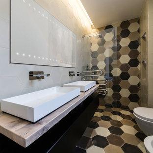 Esempio di una stanza da bagno con doccia design di medie dimensioni con ante nere, doccia a filo pavimento, WC sospeso, piastrelle beige, piastrelle bianche, piastrelle nere, piastrelle di cemento, pareti beige, pavimento in cementine, lavabo rettangolare, top in legno e ante lisce