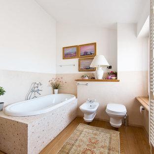 Immagine di una stanza da bagno chic con vasca da incasso, WC monopezzo, pareti rosa e parquet chiaro