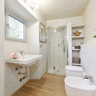 Modelo de cuarto de baño moderno con ducha empotrada, sanitario de pared, paredes blancas, suelo de madera clara y lavabo suspendido