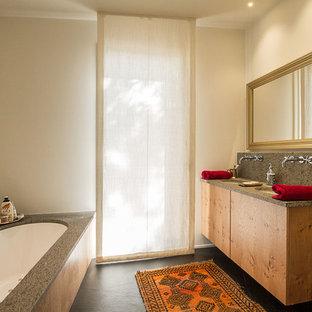 Ejemplo de cuarto de baño ecléctico con armarios con paneles lisos, puertas de armario de madera oscura, bañera encastrada sin remate, baldosas y/o azulejos grises, paredes blancas, lavabo bajoencimera, suelo negro y encimeras grises