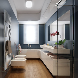 Photo of a mid-sized contemporary master bathroom in Venice with flat-panel cabinets, white cabinets, an alcove tub, a bidet, blue walls, medium hardwood floors, engineered quartz benchtops, brown floor, an integrated sink and white benchtops.