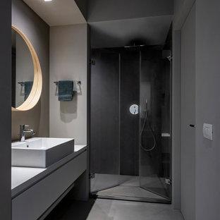 Foto di una stanza da bagno con doccia design di medie dimensioni con ante lisce, ante grigie, doccia alcova, pareti grigie, lavabo a bacinella, pavimento grigio, porta doccia a battente e top grigio