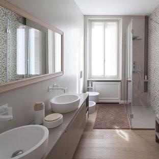 Großes Modernes Badezimmer mit flächenbündigen Schrankfronten, beigen Schränken, bodengleicher Dusche, Wandtoilette, beigefarbenen Fliesen, Zementfliesen, beiger Wandfarbe, hellem Holzboden, Aufsatzwaschbecken, Mineralwerkstoff-Waschtisch, beigem Boden und Falttür-Duschabtrennung in Mailand