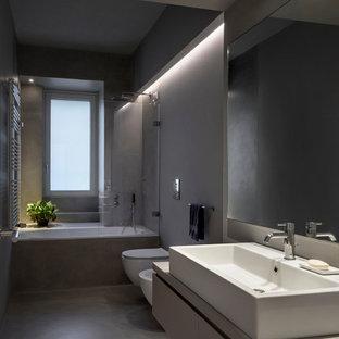 Foto di una stanza da bagno con doccia minimal di medie dimensioni con ante lisce, ante grigie, vasca ad alcova, vasca/doccia, WC sospeso, piastrelle grigie, pareti grigie, lavabo a bacinella, pavimento grigio e top grigio