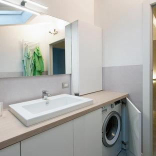 Cette image montre une salle de bain minimaliste de taille moyenne avec un placard à porte plane, des portes de placard blanches, un plan de toilette en bois, un mur gris, un sol en carrelage de porcelaine, une grande vasque et un plan de toilette beige.