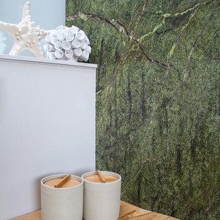 Imagen de cuarto de baño minimalista, de tamaño medio, con sanitario de pared, baldosas y/o azulejos verdes, baldosas y/o azulejos de mármol, paredes beige, suelo de baldosas de porcelana, lavabo sobreencimera, encimera de madera, suelo beige y encimeras beige