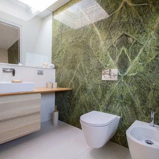 Immagine di una stanza da bagno minimal di medie dimensioni con WC sospeso, piastrelle verdi, piastrelle di marmo, pavimento in gres porcellanato, lavabo a bacinella, top in legno, pavimento beige, top beige, ante lisce, ante in legno chiaro e pareti bianche