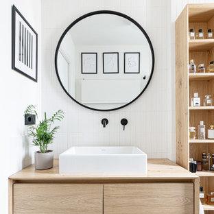 Ispirazione per una piccola stanza da bagno con doccia nordica con ante lisce, ante in legno chiaro, piastrelle bianche, pareti bianche, lavabo a bacinella, top in legno, un lavabo, mobile bagno sospeso e top beige
