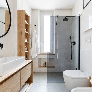 Идея дизайна: маленькая ванная комната в скандинавском стиле с плоскими фасадами, светлыми деревянными фасадами, душем без бортиков, инсталляцией, белой плиткой, удлиненной плиткой, белыми стенами, бетонным полом, душевой кабиной, настольной раковиной, столешницей из дерева, серым полом, открытым душем, тумбой под одну раковину, подвесной тумбой и многоуровневым потолком
