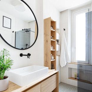 Свежая идея для дизайна: маленькая ванная комната в скандинавском стиле с плоскими фасадами, светлыми деревянными фасадами, душем без бортиков, инсталляцией, белой плиткой, удлиненной плиткой, белыми стенами, бетонным полом, душевой кабиной, настольной раковиной, столешницей из дерева, серым полом, открытым душем, тумбой под одну раковину, подвесной тумбой и многоуровневым потолком - отличное фото интерьера