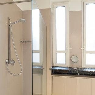 ミラノの広いコンテンポラリースタイルのおしゃれなバスルーム (浴槽なし) (フラットパネル扉のキャビネット、グレーのキャビネット、バリアフリー、分離型トイレ、ピンクのタイル、ピンクの壁、磁器タイルの床、一体型シンク、珪岩の洗面台、ベージュの床、白い洗面カウンター) の写真