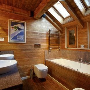 Rustik inredning av ett badrum, med ett undermonterat badkar, en vägghängd toalettstol, mellanmörkt trägolv och ett fristående handfat