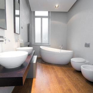 Esempio di una grande stanza da bagno padronale design con vasca freestanding, WC sospeso, pareti grigie, pavimento in legno massello medio, lavabo a bacinella, top in legno e top marrone