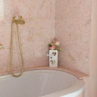 Klassisk inredning av ett stort badrum, med ett platsbyggt badkar, en toalettstol med separat cisternkåpa, rosa kakel, marmorkakel, rosa väggar, ett piedestal handfat och rosa golv