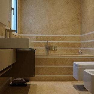 Ispirazione per una piccola stanza da bagno con doccia minimalista con ante lisce, ante marroni, vasca da incasso, doccia doppia, WC sospeso, piastrelle gialle, piastrelle in travertino, pavimento in travertino, lavabo rettangolare, top in vetro, pavimento giallo, porta doccia a battente e pareti gialle