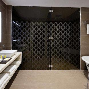 ボローニャの大きいコンテンポラリースタイルのおしゃれなマスターバスルーム (オープンシェルフ、青いキャビネット、置き型浴槽、段差なし、壁掛け式トイレ、茶色いタイル、磁器タイル、茶色い壁、無垢フローリング、ベッセル式洗面器、人工大理石カウンター、ベージュの床、開き戸のシャワー、ベージュのカウンター) の写真