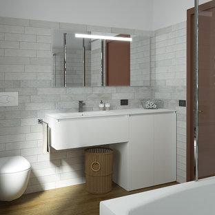 Ejemplo de cuarto de baño con ducha, moderno, pequeño, con armarios con paneles lisos, puertas de armario blancas, combinación de ducha y bañera, sanitario de pared, baldosas y/o azulejos grises, baldosas y/o azulejos de porcelana, paredes blancas, suelo de bambú, lavabo integrado, suelo marrón, ducha abierta, encimeras blancas y encimera de acrílico