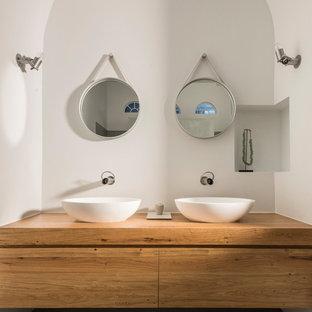 Modernes Badezimmer mit hellbraunen Holzschränken, Waschtisch aus Holz, grauem Boden, flächenbündigen Schrankfronten, weißer Wandfarbe, Aufsatzwaschbecken und beiger Waschtischplatte in Mailand