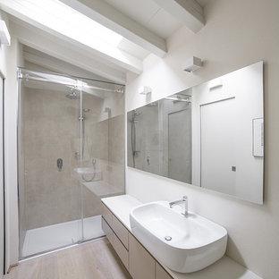 Foto di una piccola stanza da bagno padronale contemporanea con ante lisce, ante grigie, piastrelle grigie, piastrelle in gres porcellanato, pareti bianche, parquet chiaro, lavabo a bacinella, top in superficie solida, doccia alcova e porta doccia scorrevole