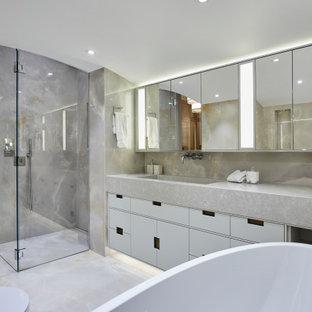 Cette image montre une salle de bain design avec un placard à porte plane, des portes de placard blanches, un carrelage gris, un lavabo intégré, un sol gris, une cabine de douche à porte battante, un plan de toilette gris, meuble simple vasque, meuble-lavabo suspendu et un plafond voûté.