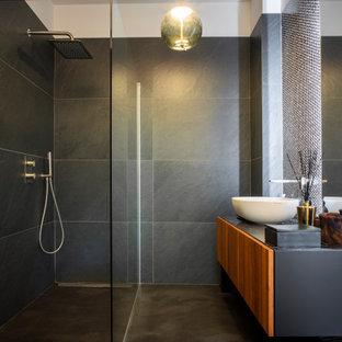 Foto di una stanza da bagno contemporanea con ante lisce, ante in legno scuro, doccia a filo pavimento, piastrelle grigie, lavabo a bacinella, pavimento grigio, doccia aperta, top nero, un lavabo e mobile bagno sospeso