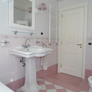 Diseño de cuarto de baño principal, romántico, de tamaño medio, con armarios tipo vitrina, puertas de armario blancas, bañera encastrada, sanitario de dos piezas, baldosas y/o azulejos rosa, baldosas y/o azulejos de cerámica, paredes multicolor, suelo de baldosas de porcelana, lavabo con pedestal y suelo rosa