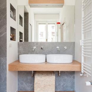 Ispirazione per una stanza da bagno contemporanea con piastrelle grigie, pareti bianche, pavimento in legno massello medio, lavabo a bacinella, top in legno, pavimento marrone, top beige, nicchia e due lavabi