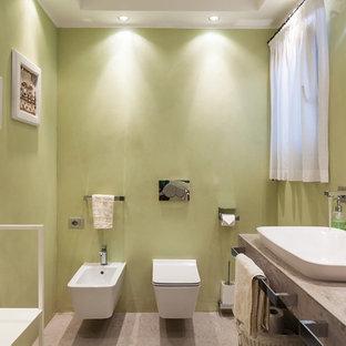 Imagen de cuarto de baño actual, de tamaño medio, con sanitario de pared, paredes verdes, lavabo sobreencimera y encimera de mármol