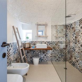 Mediterranes Duschbad mit Eckdusche, Bidet, farbigen Fliesen, Zementfliesen, weißer Wandfarbe, Aufsatzwaschbecken, Waschtisch aus Holz, beigem Boden, offener Dusche und brauner Waschtischplatte in Bari