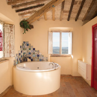 Foto di una stanza da bagno mediterranea di medie dimensioni con pareti blu, pavimento in terracotta, pavimento rosso, nessun'anta, ante in legno bruno, vasca ad angolo, doccia aperta, lavabo a bacinella e top in legno
