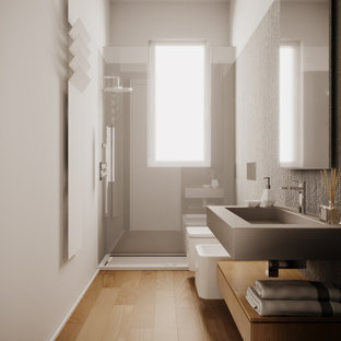 Inspiration for a small contemporary 3/4 bathroom in Milan with flat-panel cabinets, light wood cabinets, a curbless shower, a wall-mount toilet, gray tile, porcelain tile, white walls, porcelain floors, a drop-in sink, solid surface benchtops, a sliding shower screen, white benchtops, a single vanity, a floating vanity and recessed.