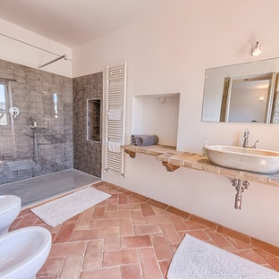 Photo of a medium sized mediterranean ensuite bathroom in Other with a built-in shower, a wall mounted toilet, ceramic tiles, terracotta flooring and a vessel sink.
