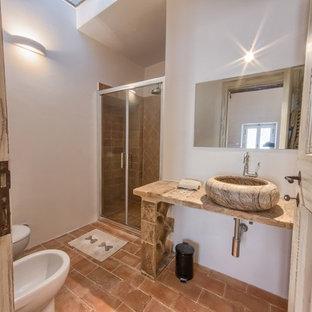Mittelgroßes Mediterranes Duschbad mit bodengleicher Dusche, Wandtoilette, Terrakottafliesen, Terrakottaboden und Aufsatzwaschbecken in Sonstige