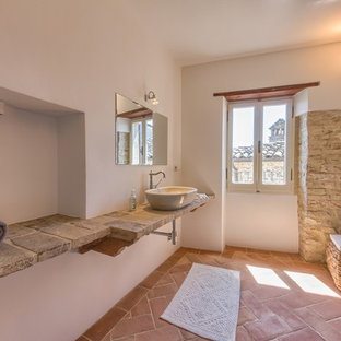 This is an example of a medium sized mediterranean ensuite bathroom in Other with a built-in shower, a wall mounted toilet, ceramic tiles, terracotta flooring and a vessel sink.