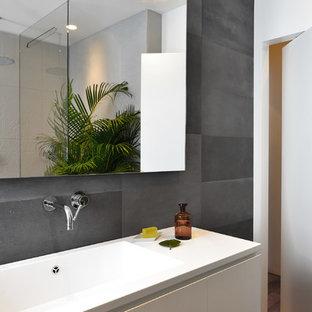 Idéer för ett mellanstort modernt badrum, med släta luckor, vita skåp, mörkt trägolv, ett integrerad handfat, stenkakel och vita väggar