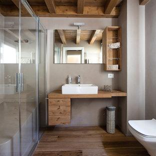 Bild på ett stort rustikt badrum, med släta luckor, skåp i mellenmörkt trä, en hörndusch, en vägghängd toalettstol, grå väggar, mellanmörkt trägolv och ett fristående handfat